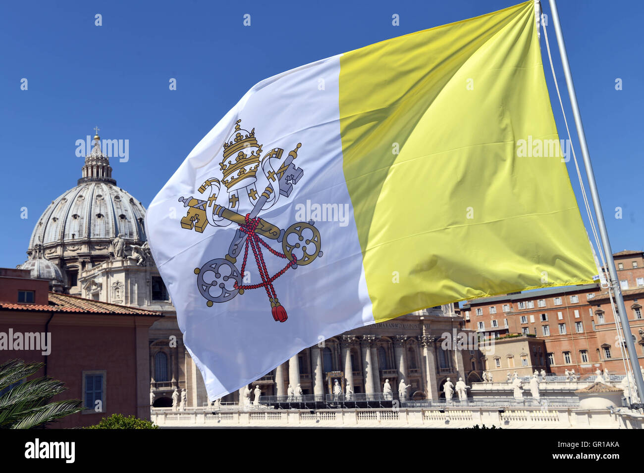 A flag with the coat of arms of Vatican City waves in Vatican City, 02 September 2016. St. Peter's Basilica can Stock Photo