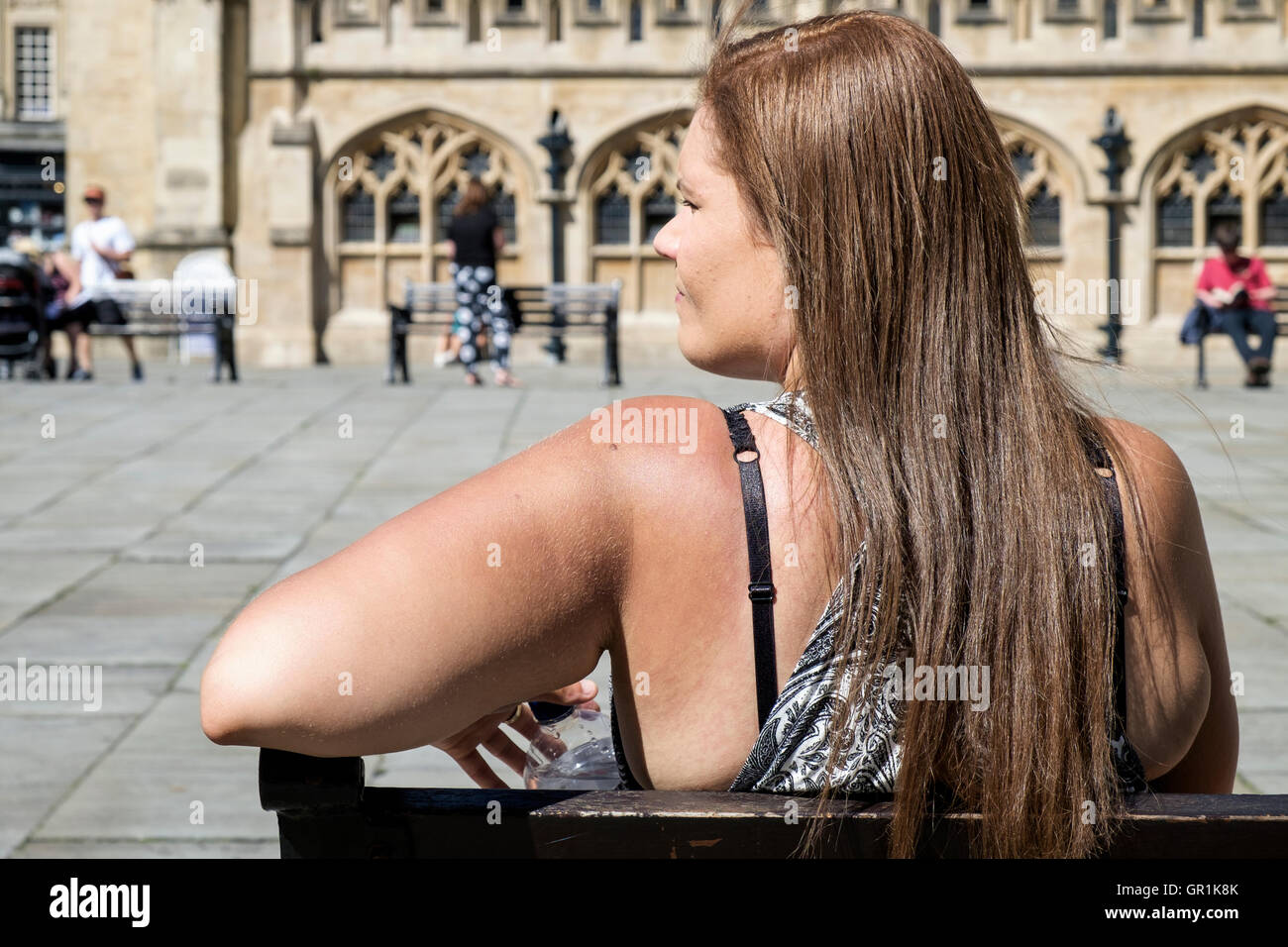 Bath,England, UK.  A woman is pictured in front of Bath Abbey enjoying the hot weather. - Stock Image