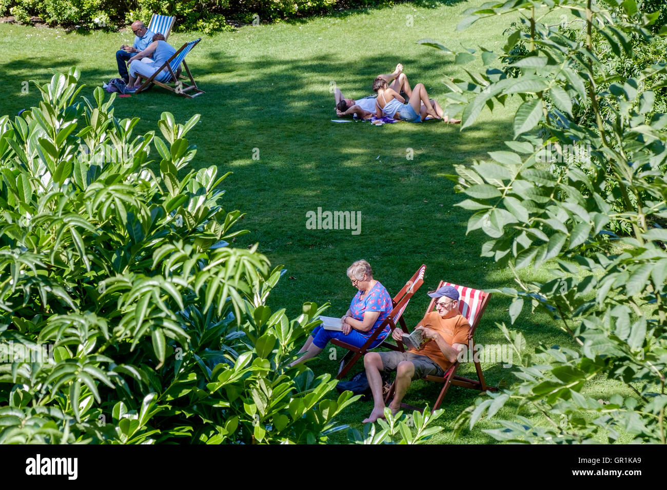 Bath,Somerset,England, UK. People are pictured sitting in dekchairs in Parade Gardens enjoying the hot weather. - Stock Image