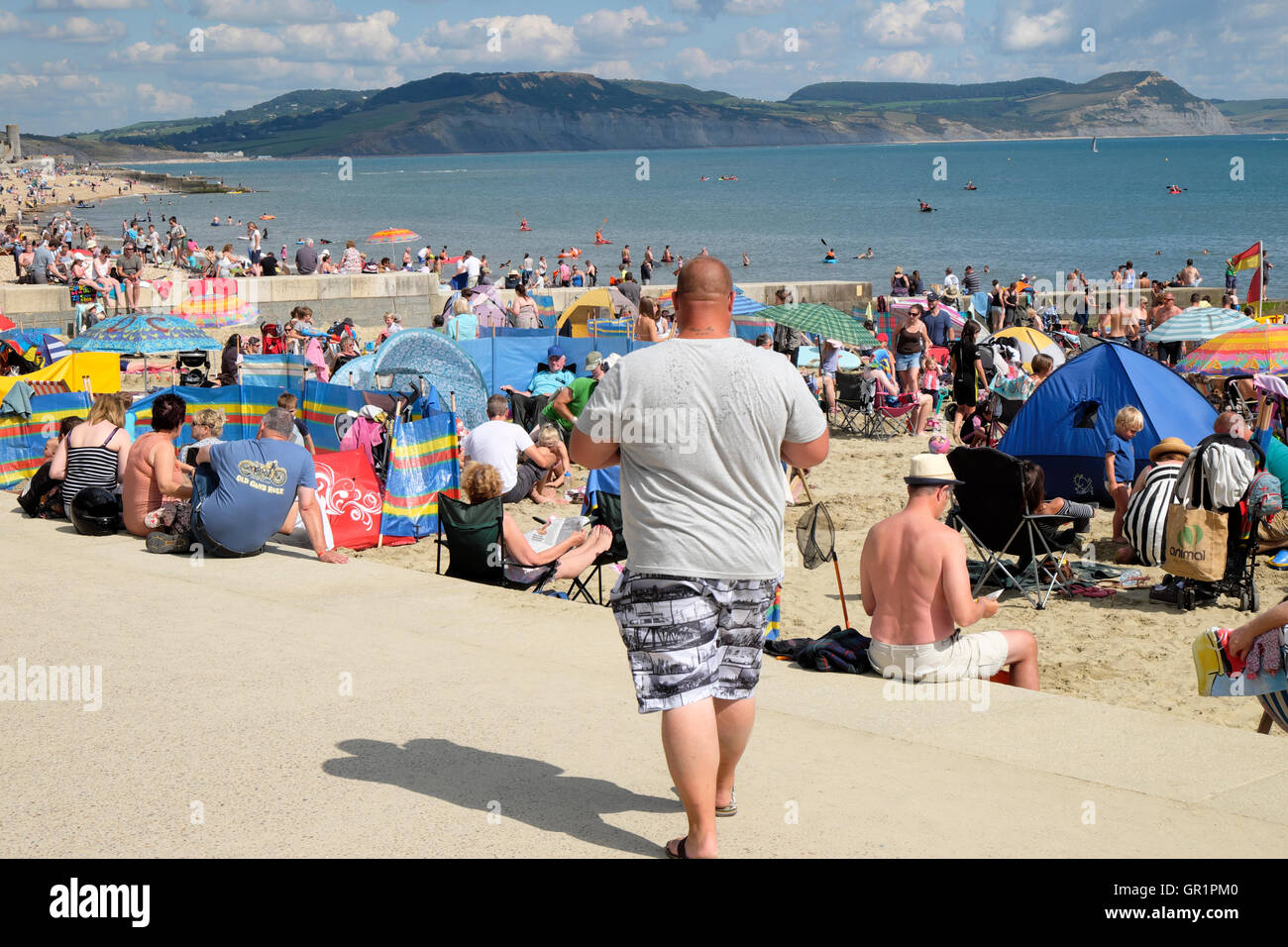 Crowd of people on the seafront beach at Lyme Regis, Dorset, England UK  KATHY DEWITT - Stock Image