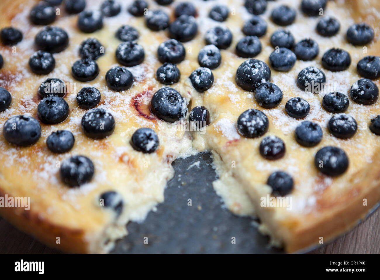 Cut blueberry pie on plate. Homebaked pastry, delicious dessert. Yummy organic food with lots of sugar, fresh berries - Stock Image