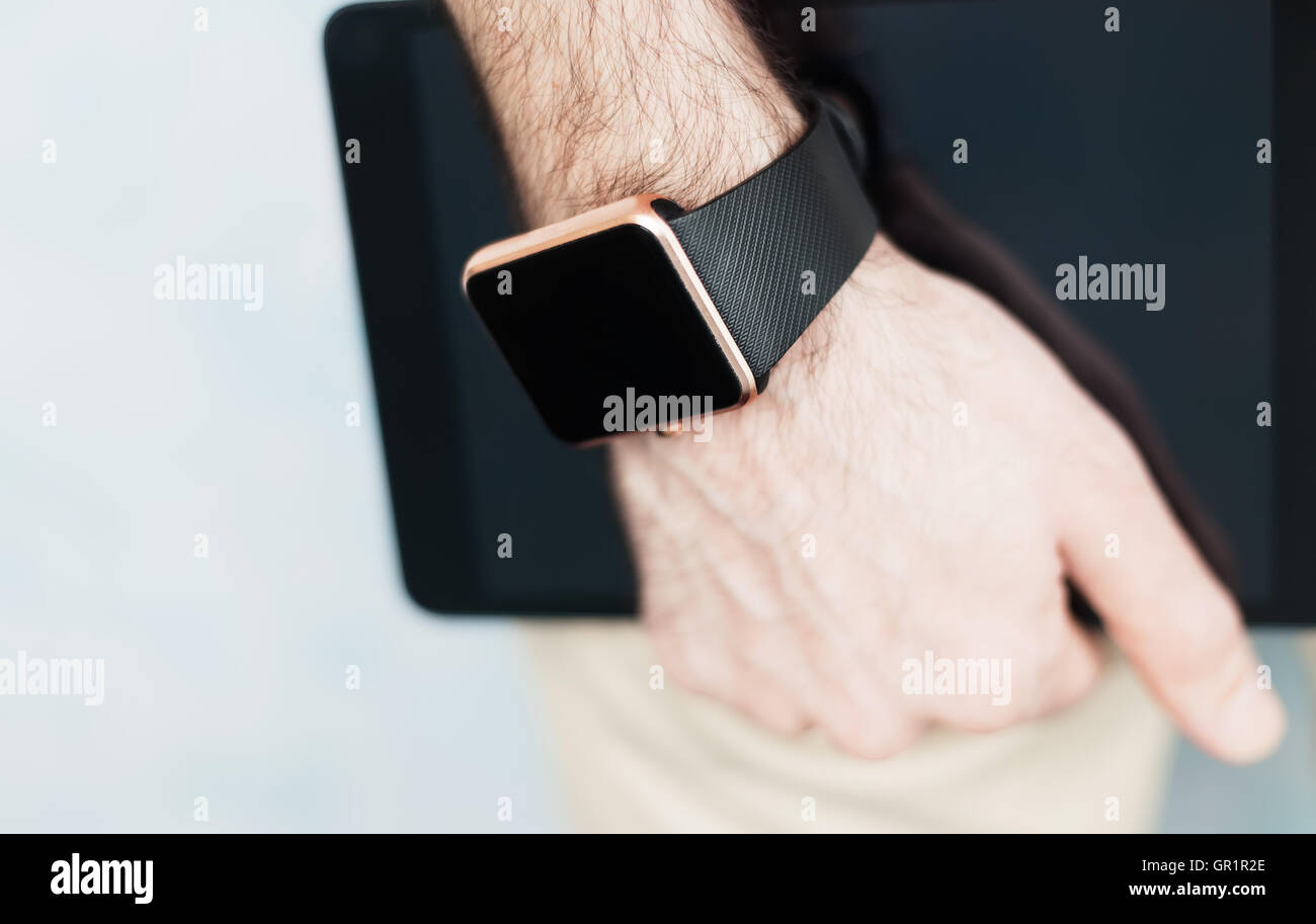 Male hand holding two modern digital devices to be always connected to internet and social media - trendy smart - Stock Image