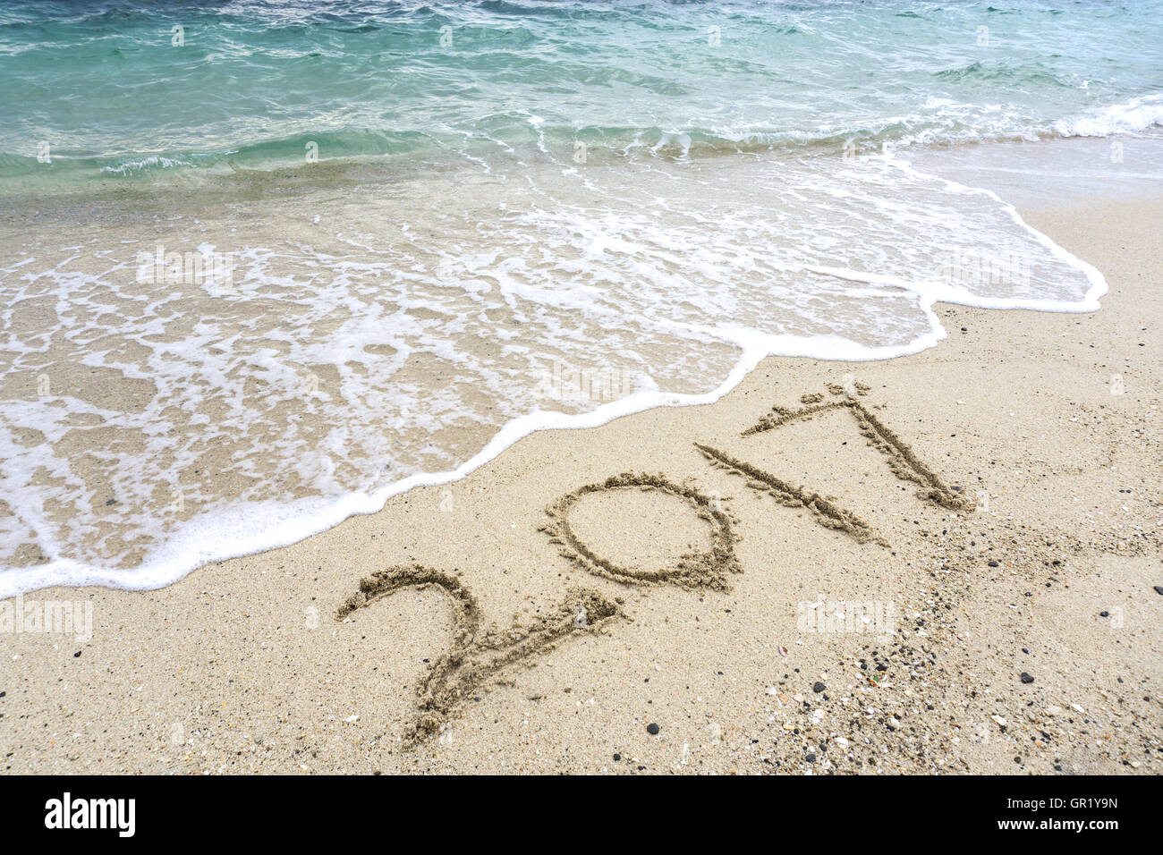 Number 2017 written on a sand beach with sea waves, Happy New Year concept. - Stock Image