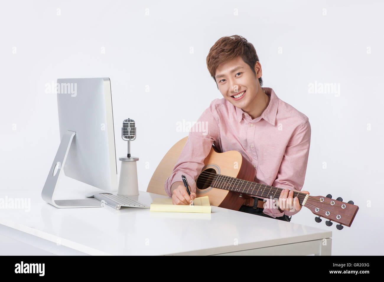 Young smiling mna playing a guitar with computer and microphone - Stock Image