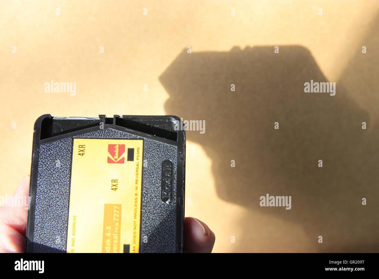Retro seventies Super 8 analogue/analog cine camera movie film cartridge with shadow on wall. - Stock Image