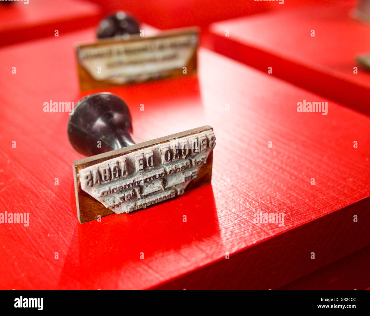 Rubber Stamps on Red. A pair of rubber stamps displayed on a bright red board. Seggao de Aghas. Thinking Section. - Stock Image
