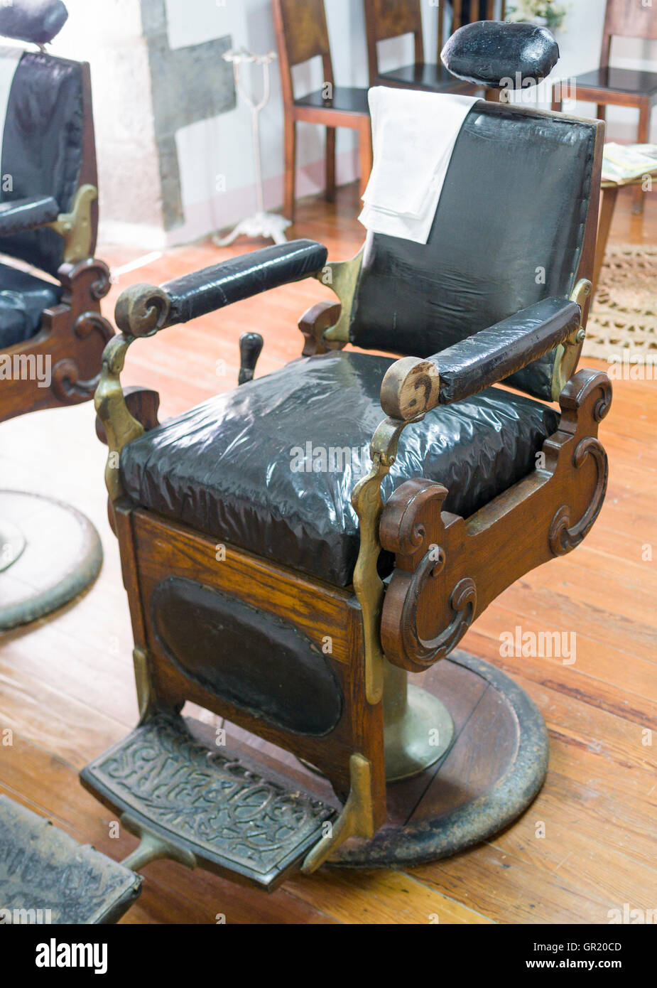 Antique Barber's Chair. The chair seems to be covered with shiny plastic  over the original - Old Antique Barber Chair Stock Photos & Old Antique Barber Chair