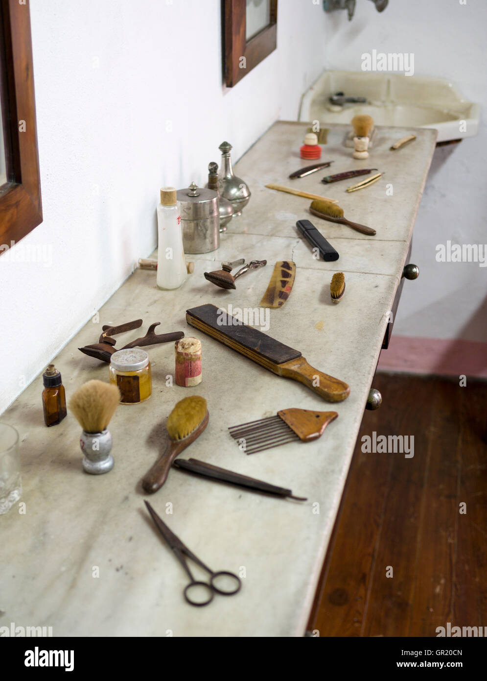 An array of antique barber's tools. Displayed on marble shelf the collection includes brushes, scissors, clippers, - Stock Image