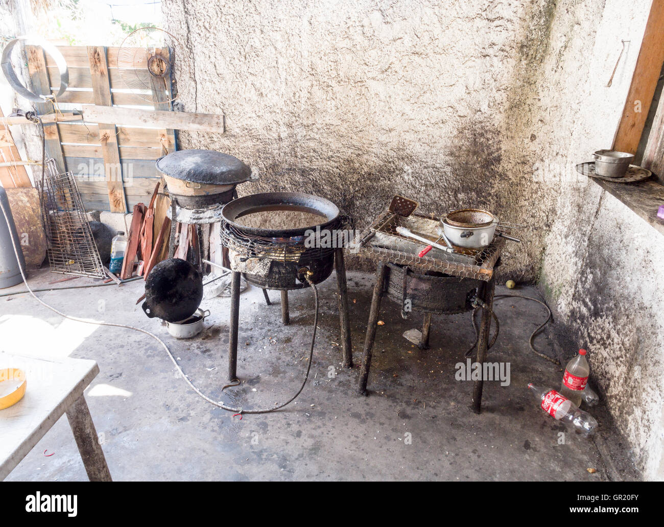Getting Ready to Cook: Heating the Oil. A propane burner heats a large vat of oil in a rough kitchen on the harbour. - Stock Image