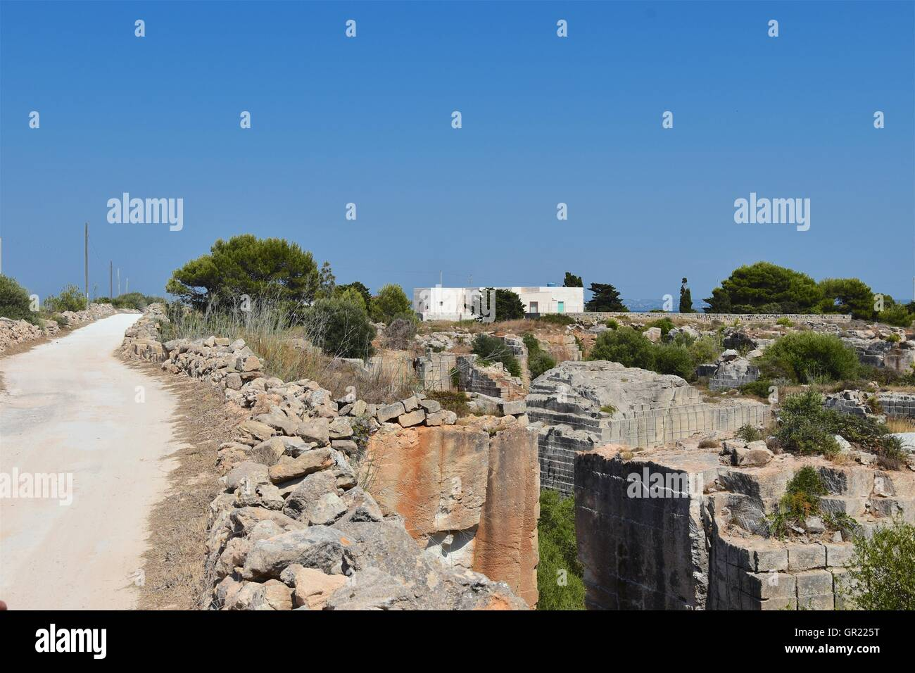 Road though desert landscape with mountains. Favignana, Sicily, Italy - Stock Image