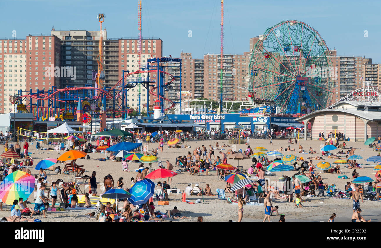 Coney Island beach with the boardwalk and Luna Park rides in the background. New York. - Stock Image