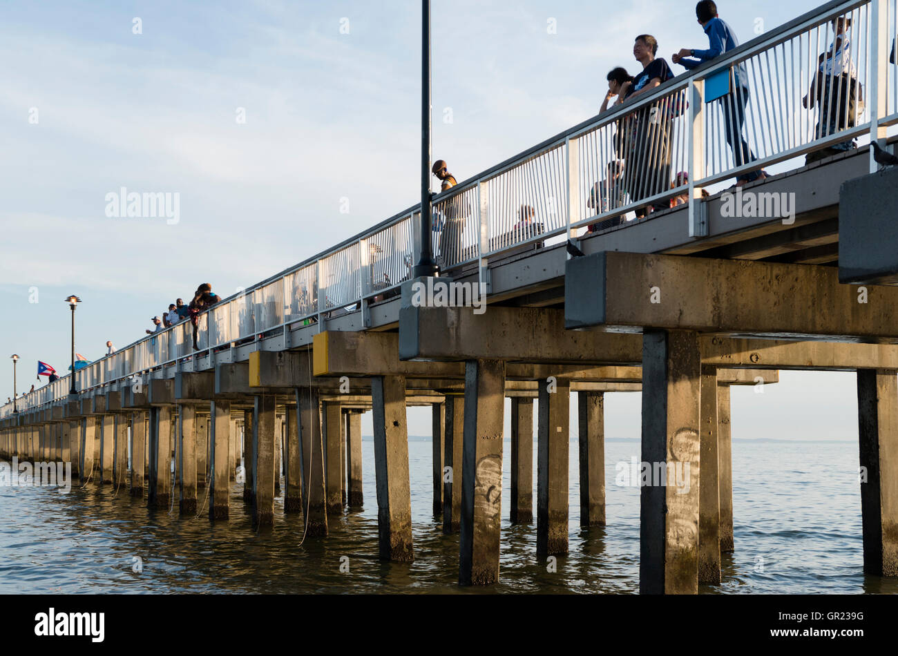 People looking out to sea on the Steeplechase wooden pier on Coney Island beach and boardwalk, New York Stock Photo