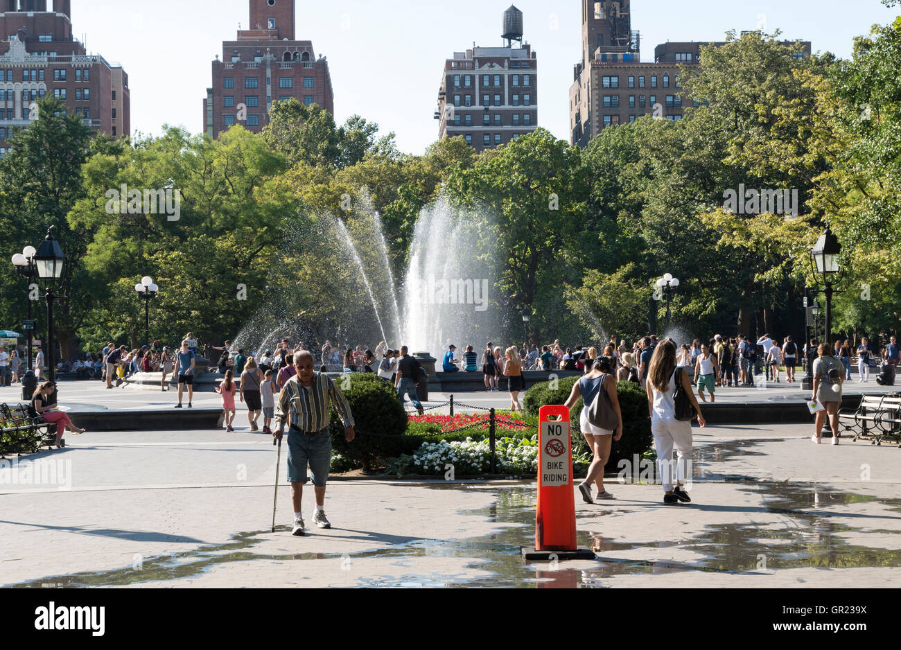 Washington Square Park in Summer with people enjoying hot weather around the water fountain. - Stock Image