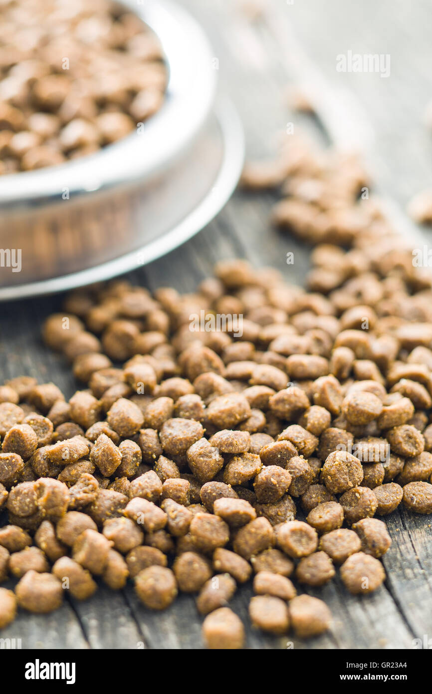 Dried food for dogs or cats on old wooden table. - Stock Image
