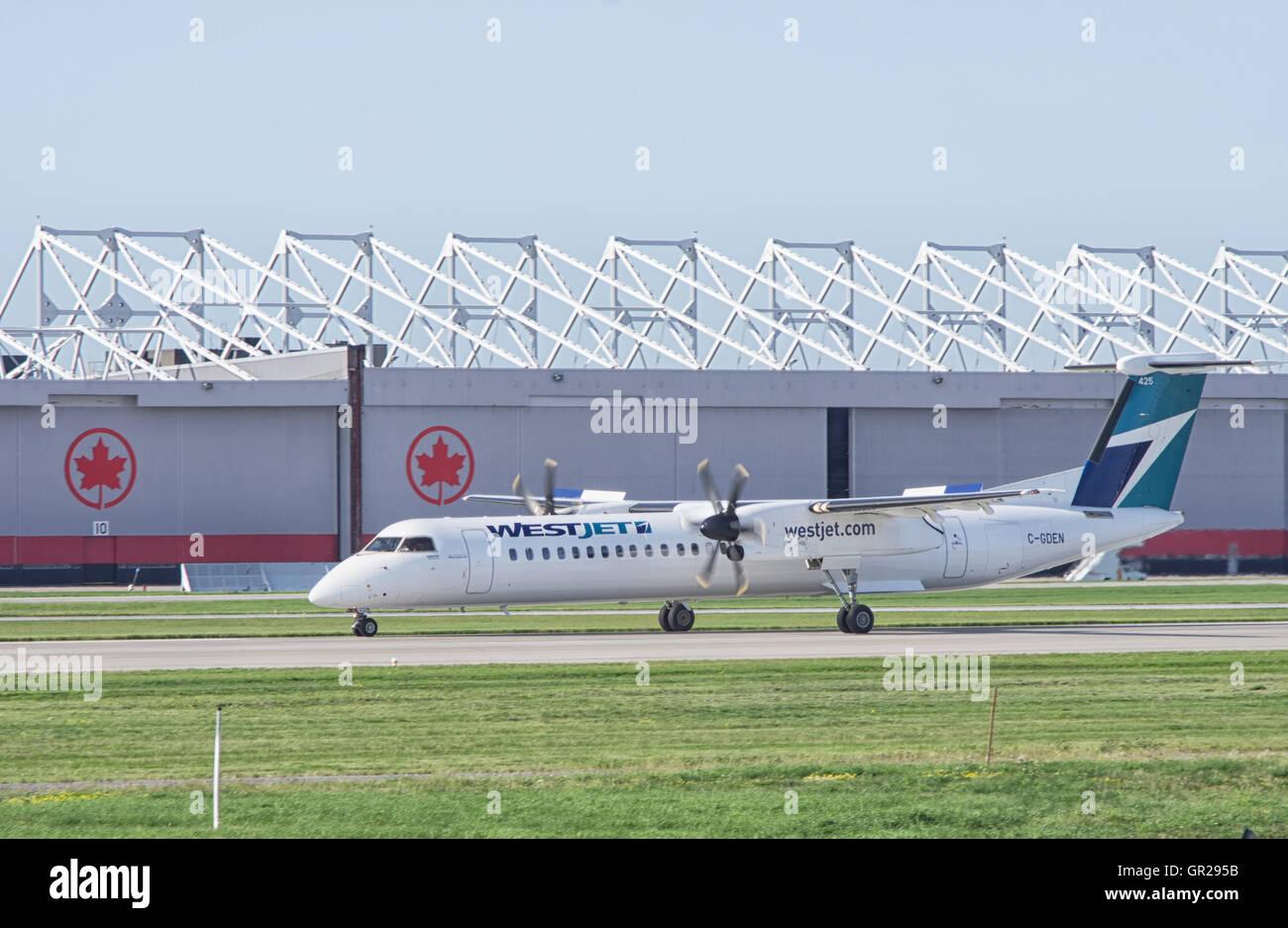 Westjet Turboprop engine aircraft departing near an Air Canada hangar at Montreal Pierre Elliott Trudeau - Stock Image