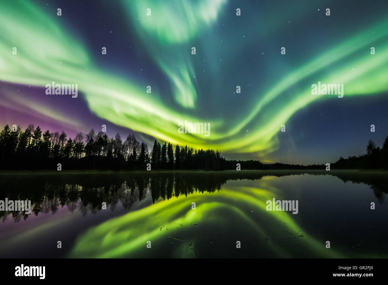 Northern Lights over a lake in Oulu, Finland - Stock Image