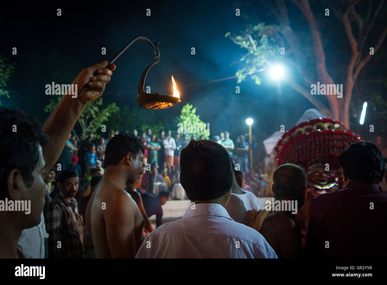 A man holds a flame aloft to illuminate the proceedings at a theyyam ritual in a northern Keralan village near Kannur - Stock Image