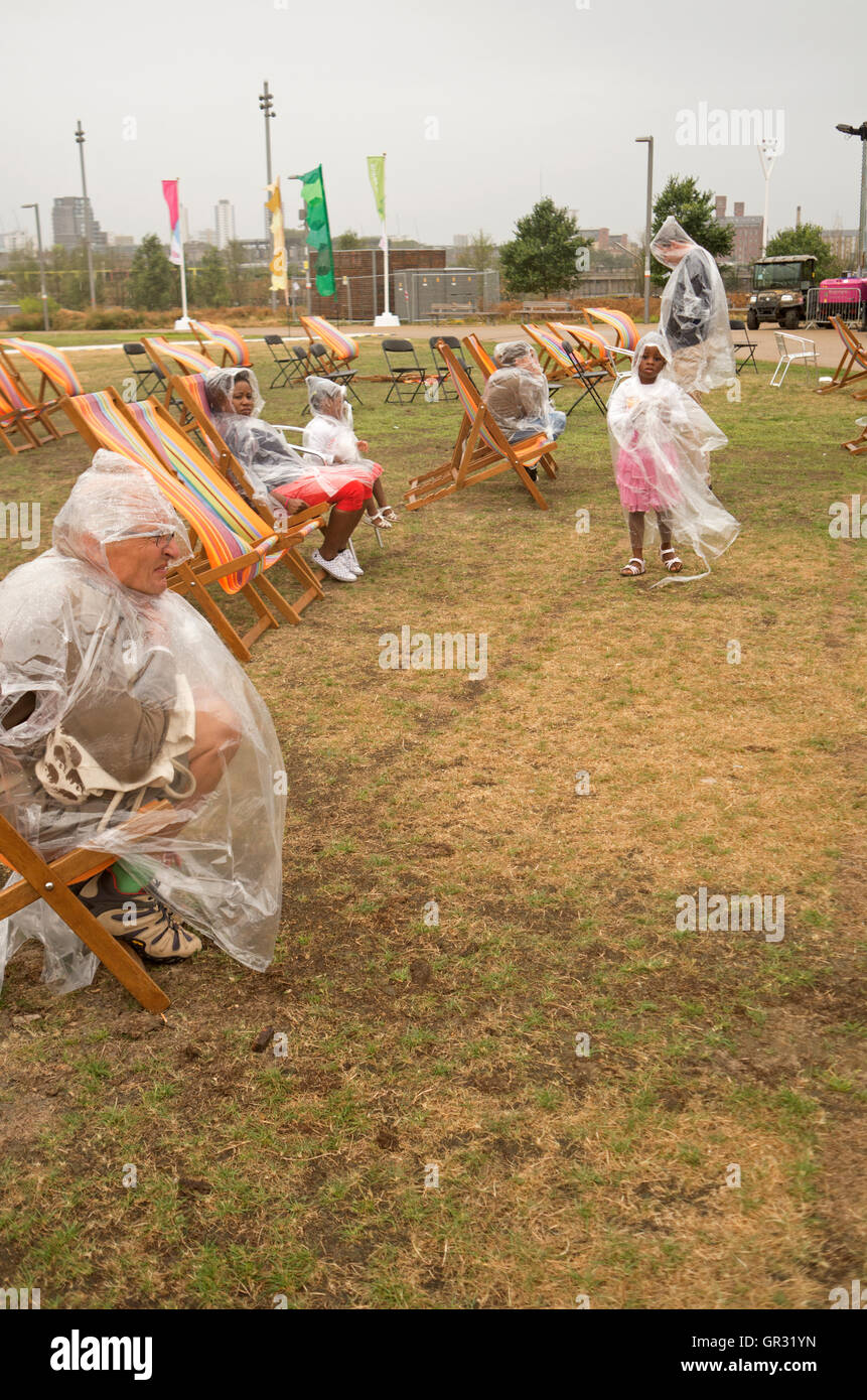 An audience in rain ponchos at the National Paralympics Day Liberty Festival in Olympic Park, London. - Stock Image