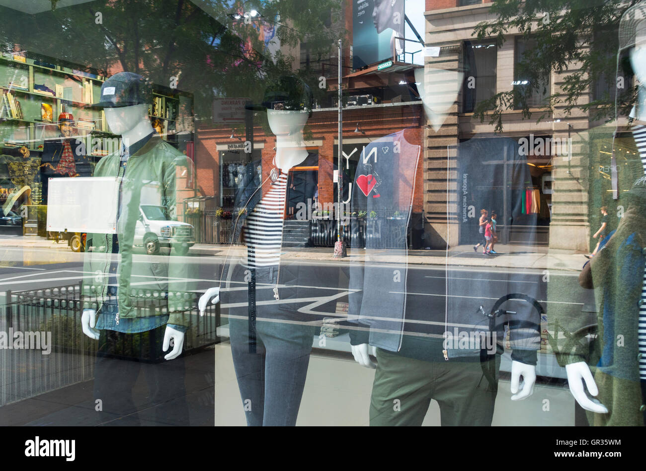 Street life reflected in the window of a men's fashion store in New York City - Stock Image