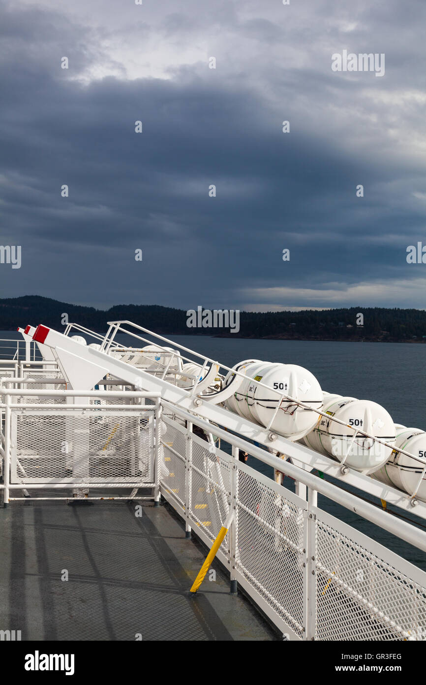 Life raft launching ramps on a ferry boat under storm clouds Stock Photo