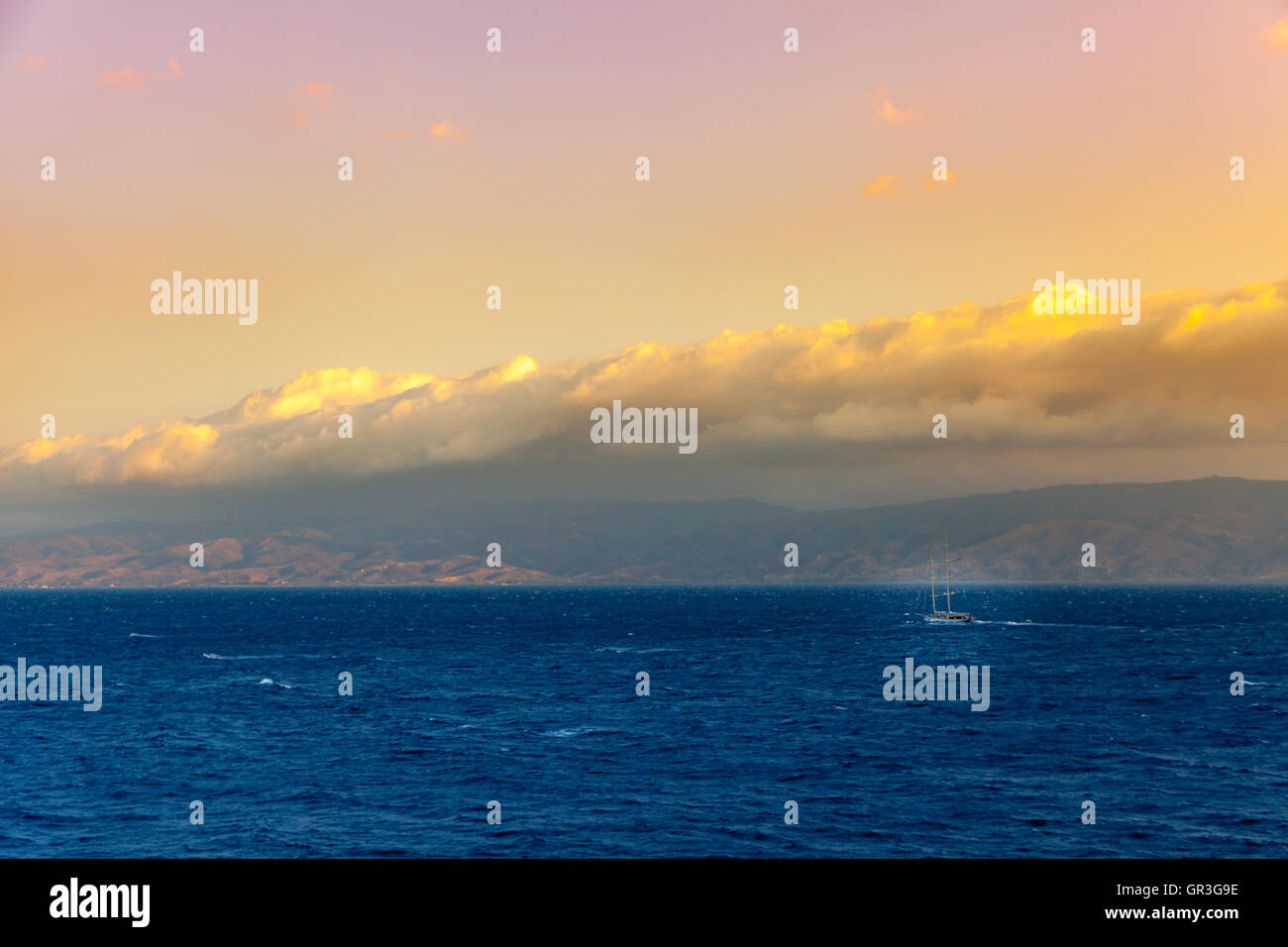 A sailing ship is passing near Hydra greek island with Peloponnese in background. - Stock Image