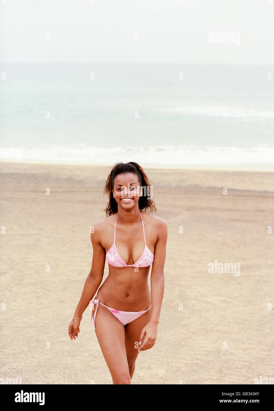 A young African woman walks on Norte Baia beach on the island of Sao Vincente, Cape Verde Islands , Africa. - Stock Image