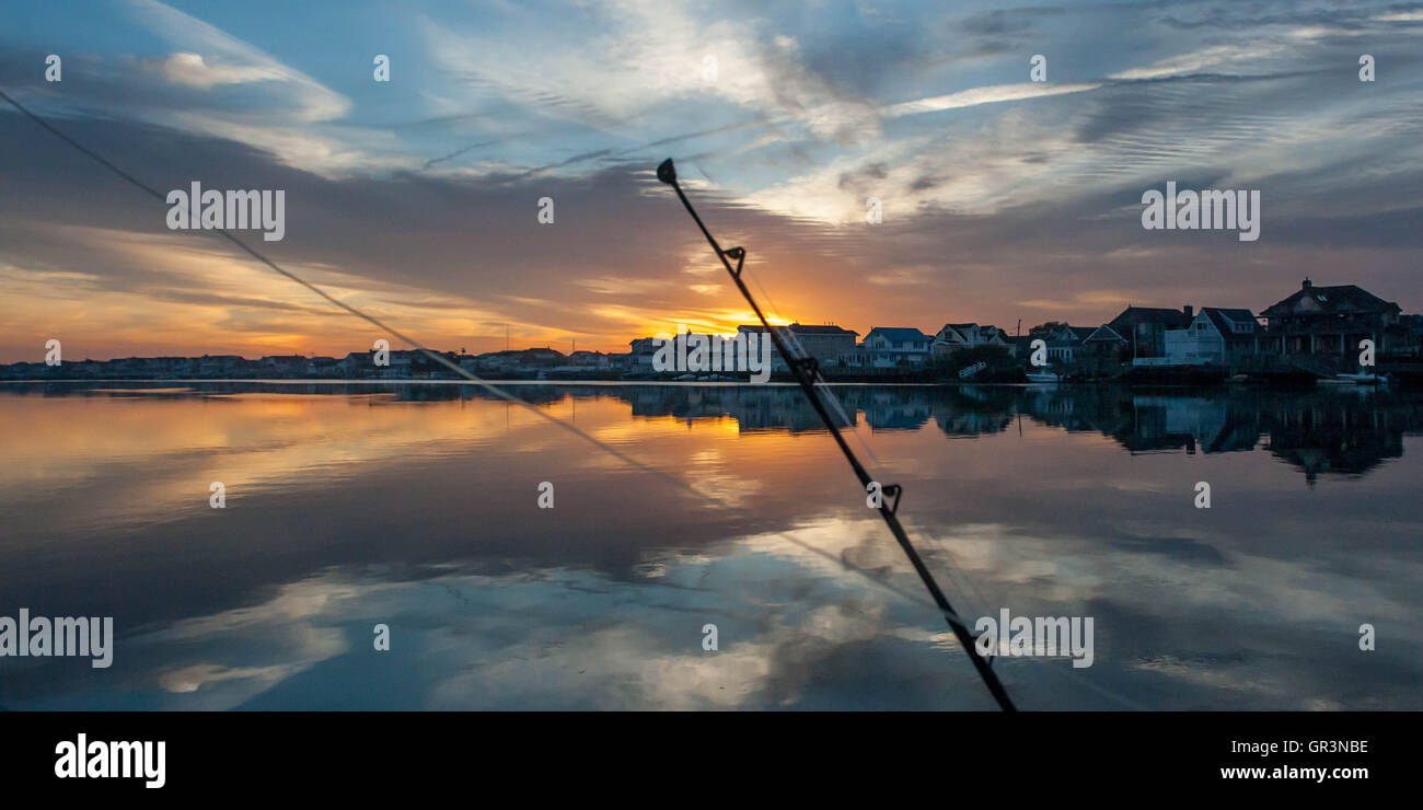 A fishing rod is silhouetted at sunrise in Stone Harbor, New Jersey United States | sunset boating on the bay | - Stock Image