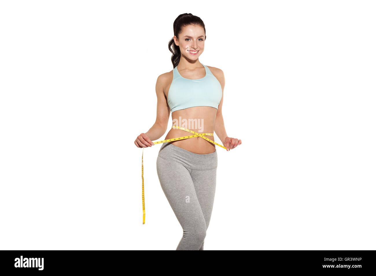 weight loss, sports girl measuring her waist, training in the gym, workout abdominals - Stock Image