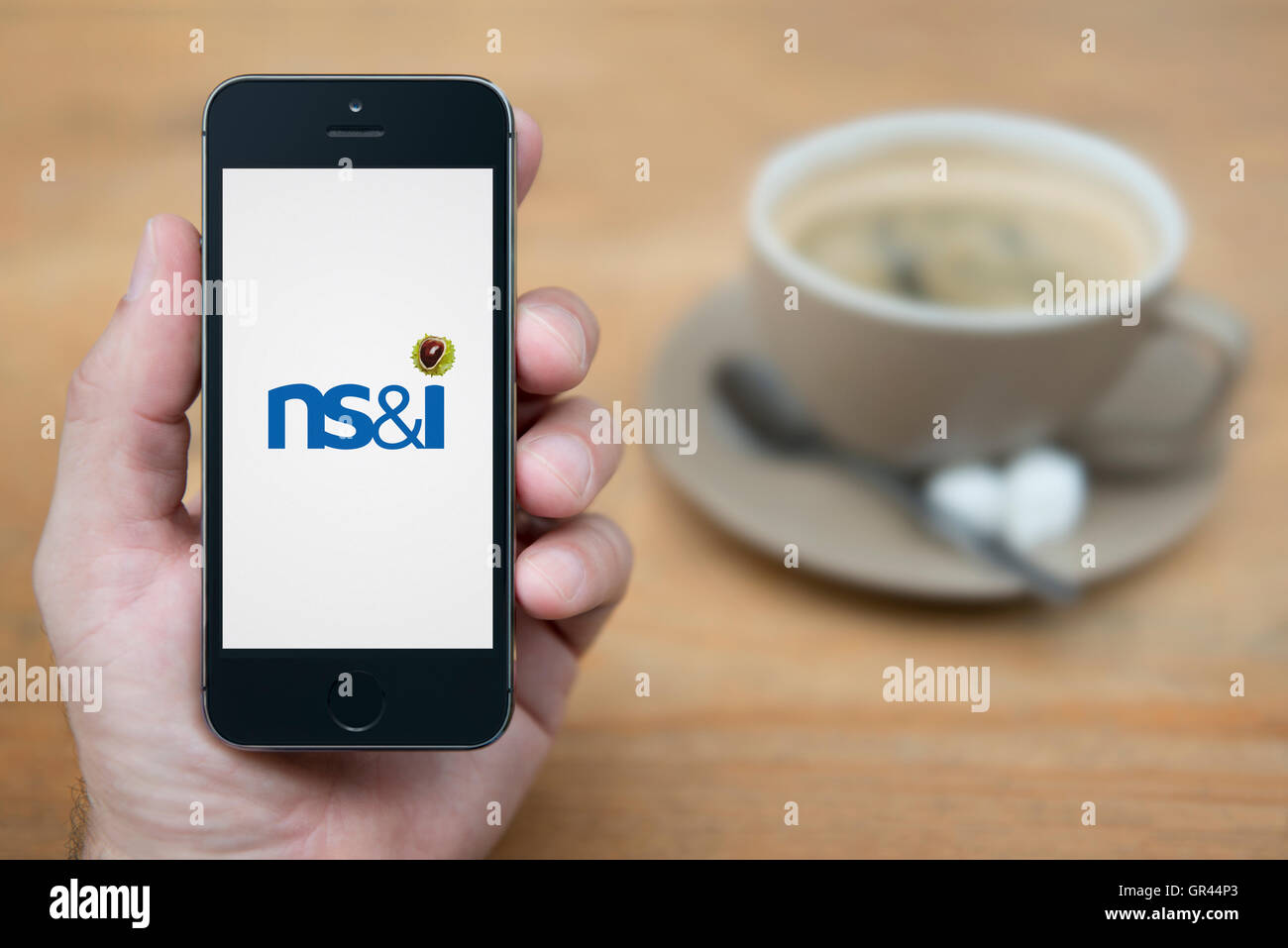 A man looks at his iPhone which displays the UK Government National Savings and Investments NS&I logo (Editorial - Stock Image