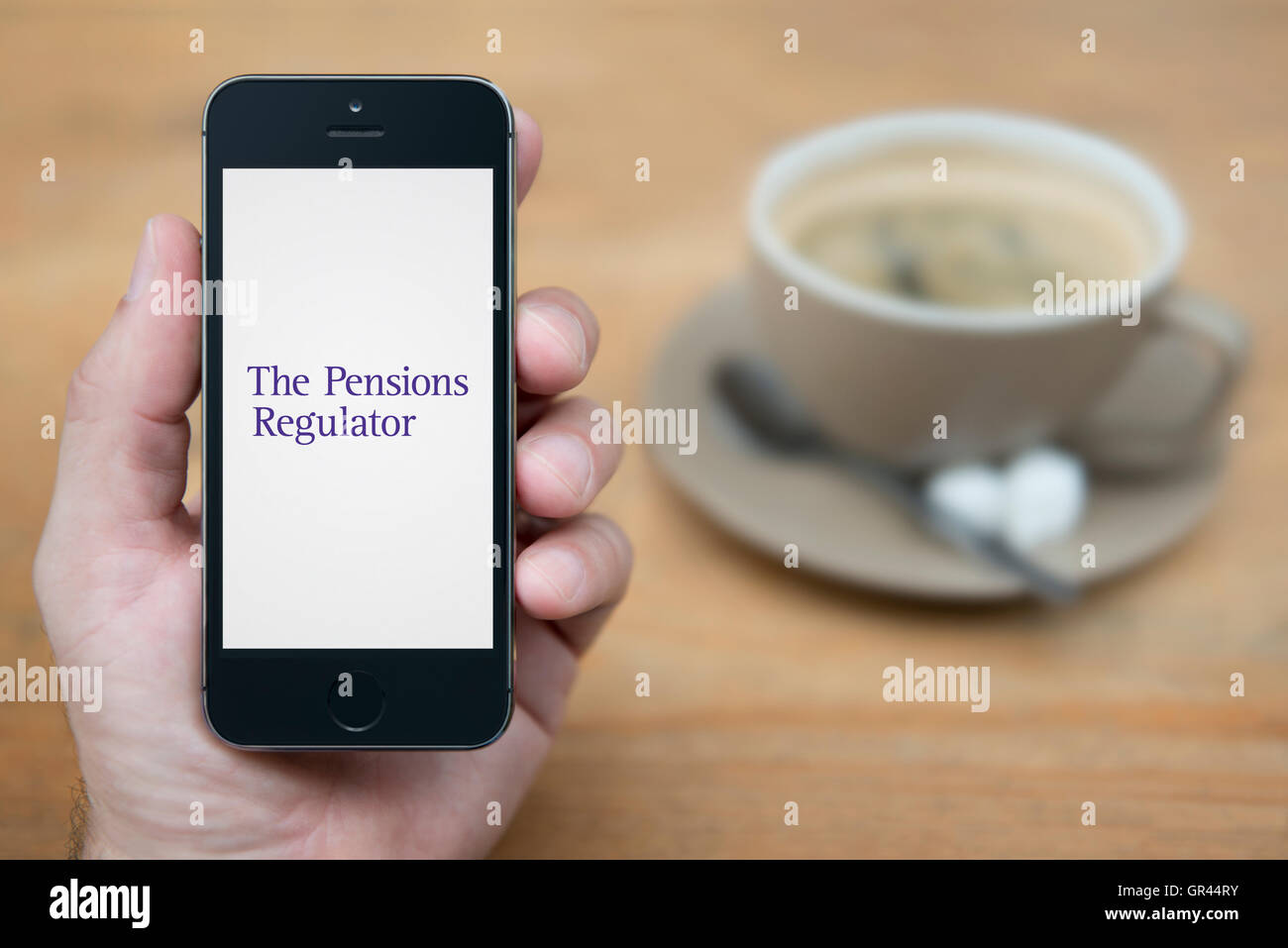 A man looks at his iPhone which displays the The Pensions Regulator logo (Editorial use only). - Stock Image