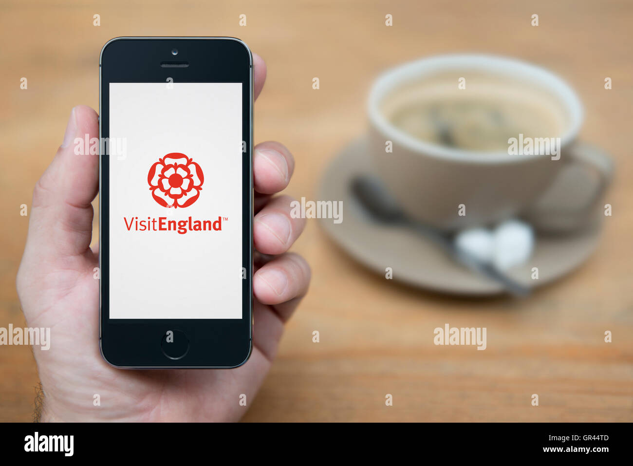 A man looks at his iPhone which displays the Visit England logo (Editorial use only). - Stock Image