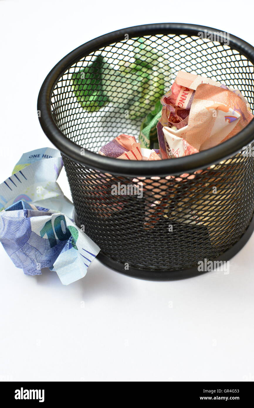 Wasting money concept. Throwing money away. Money in wastepaper basket. Losing money. wasteful spending. wasteful Stock Photo