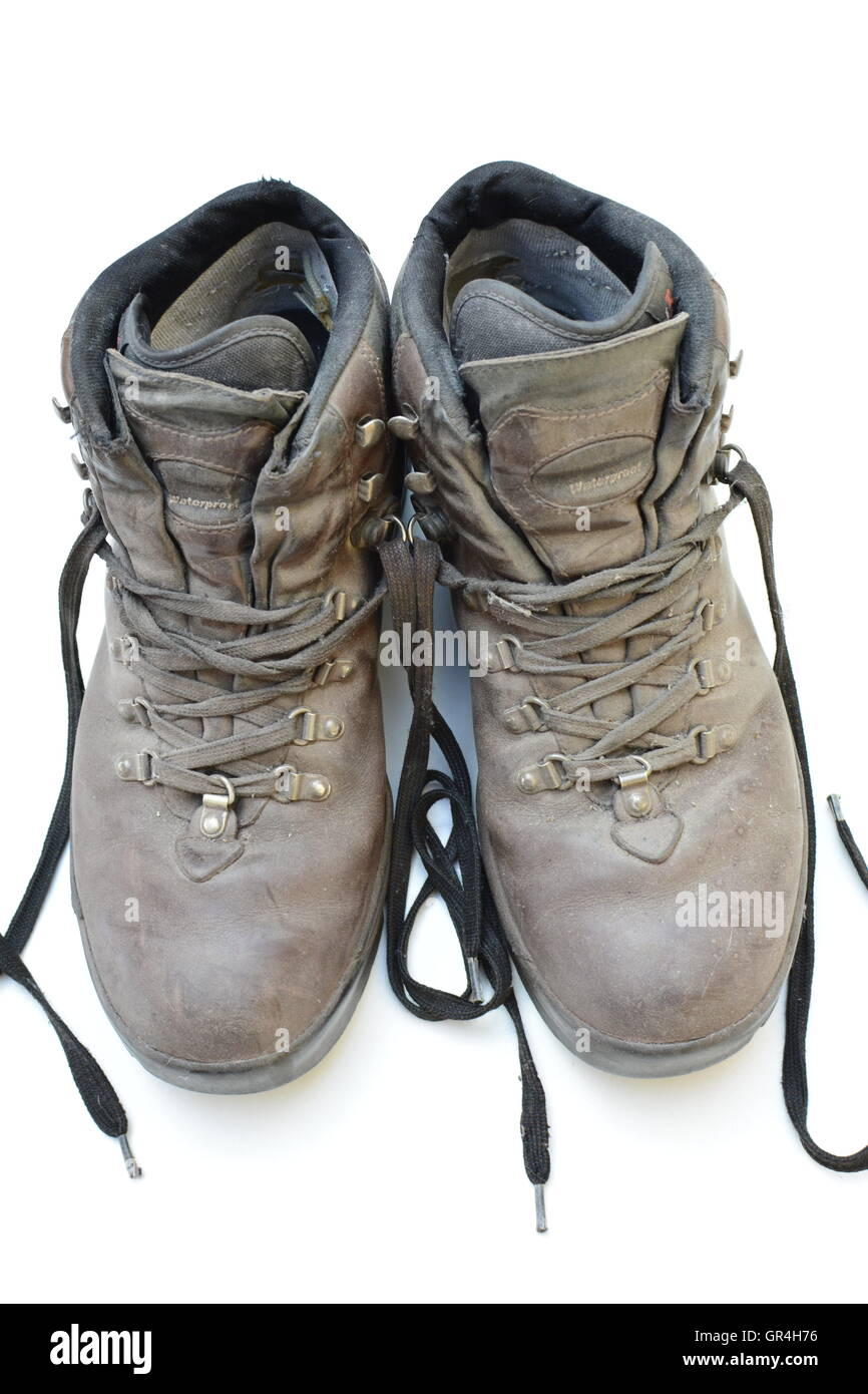 Dirty old boots isolated on white background hiking style. Bon voyage. Hiking style used boots, it was a great trip. Stock Photo