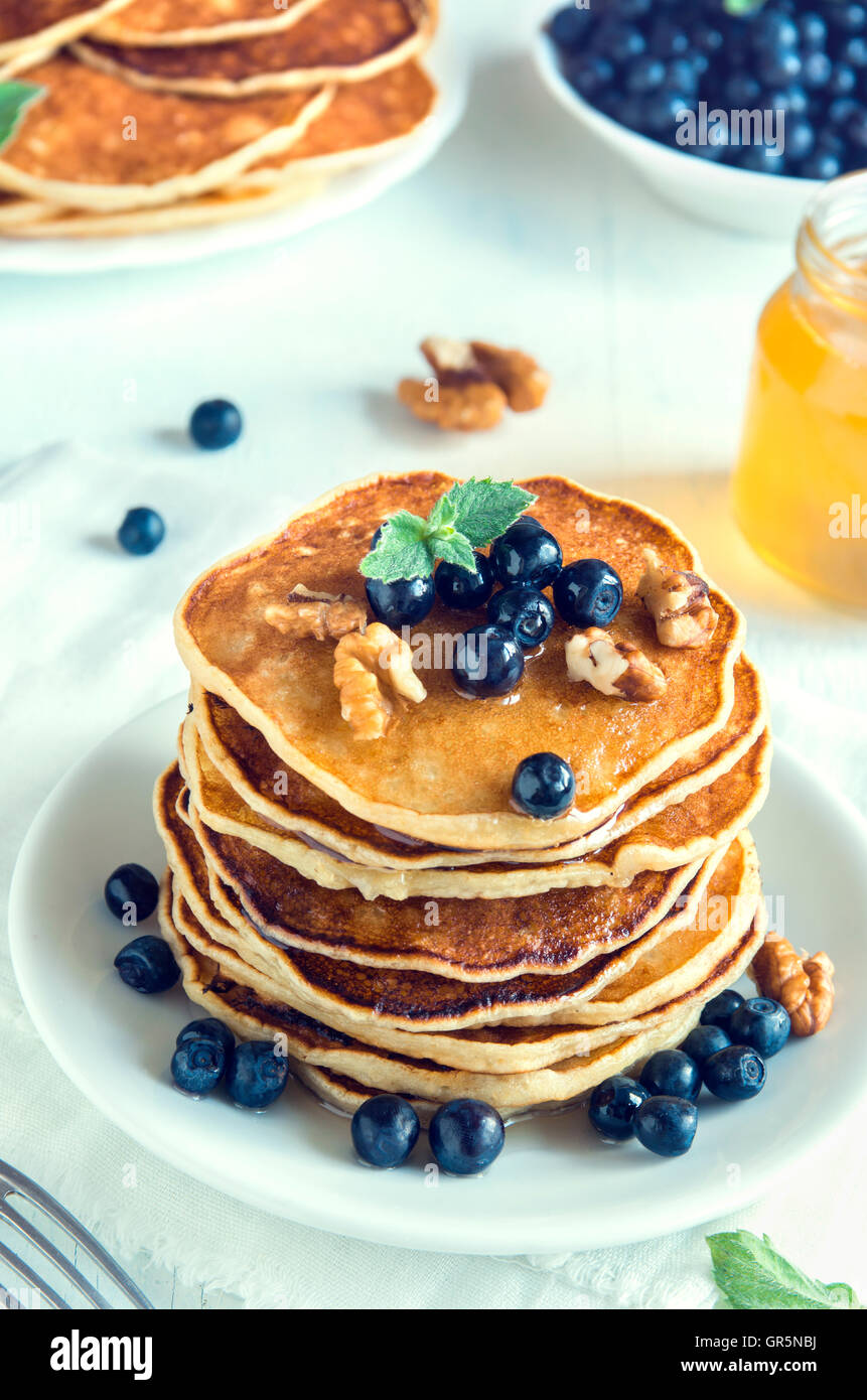 Homemade pancakes with blueberry, honey and walnuts for breakfast - Stock Image