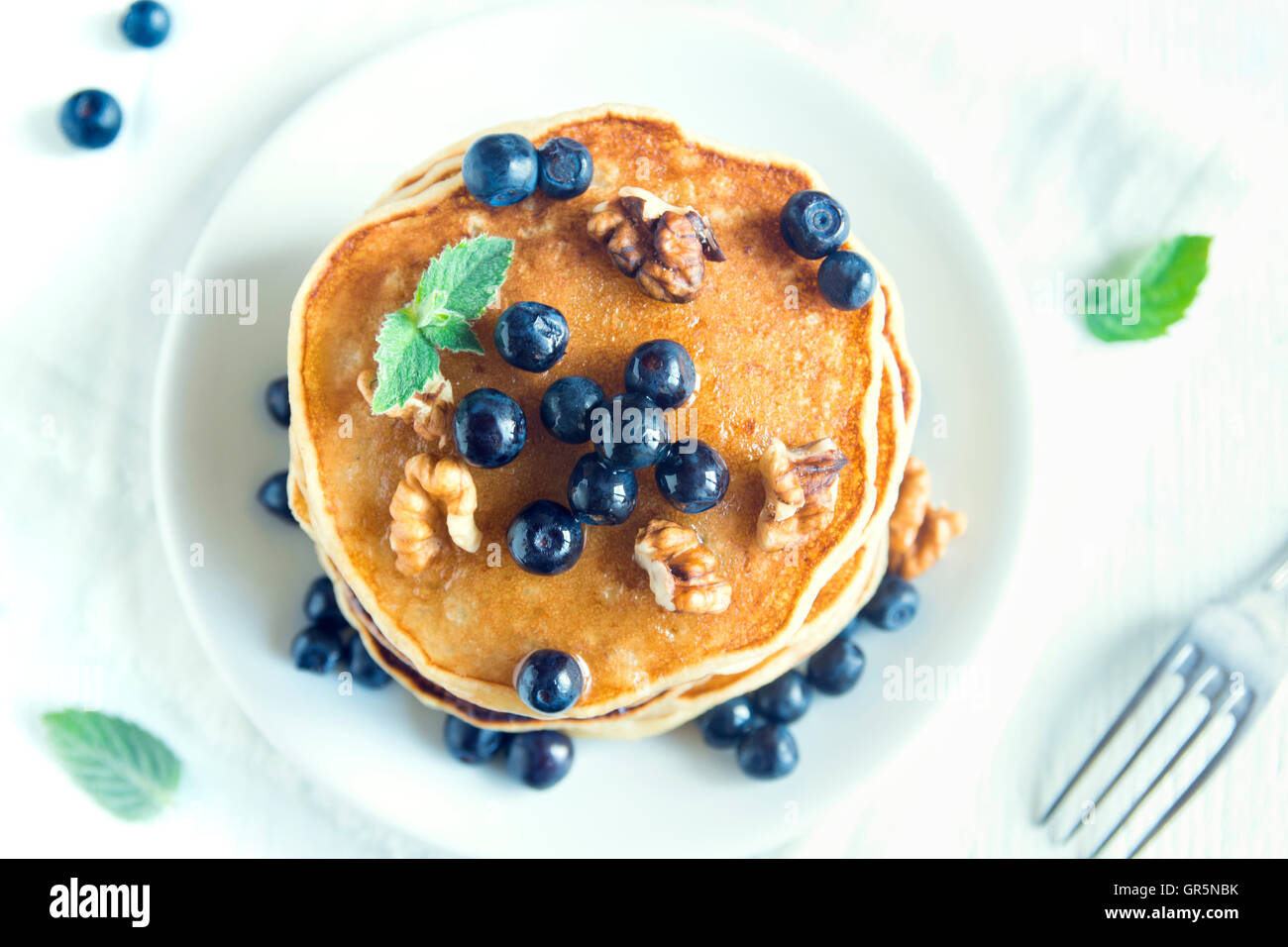 Homemade pancakes with blueberry, honey and walnuts for breakfast (top view) - Stock Image
