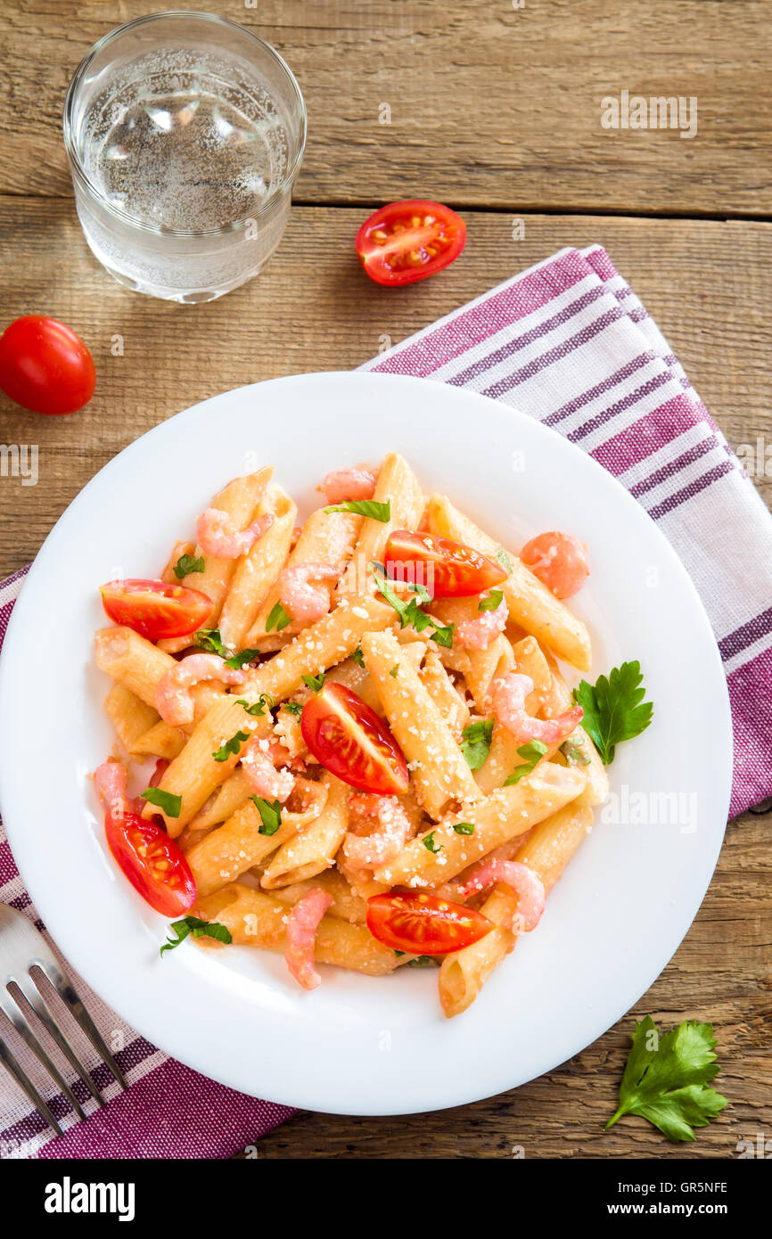 Penne pasta with shrimps, tomato sauce, parsley and grated parmesan cheese over rustic wooden background - Stock Image