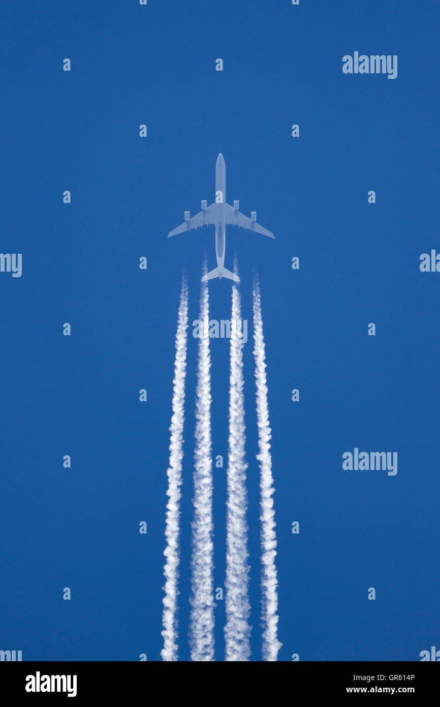 Lufthansa Airlines Airbus A340 aircraft at cruising altitude with a long white contrail forming behind the aircraft. - Stock Image