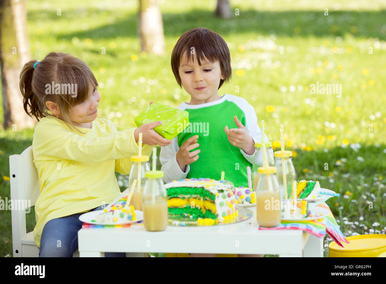 Happy sweet preschool children, friends and relatives, celebrating fifth birthday of cute boy, outdoor in blooming Stock Photo