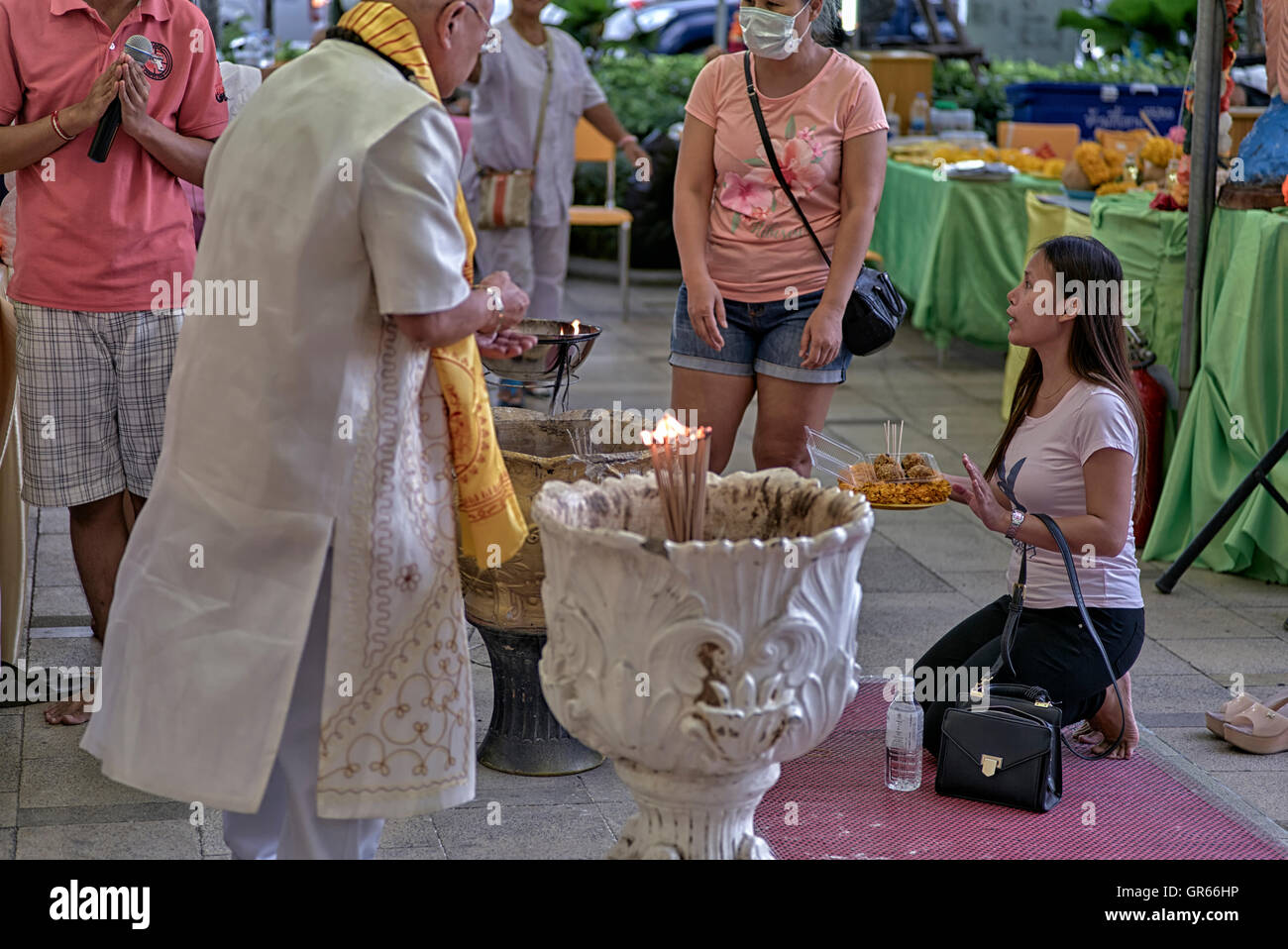 Thai woman kneeling and offering merit at a Buddhist shrine. Thailand S. E. Asia - Stock Image
