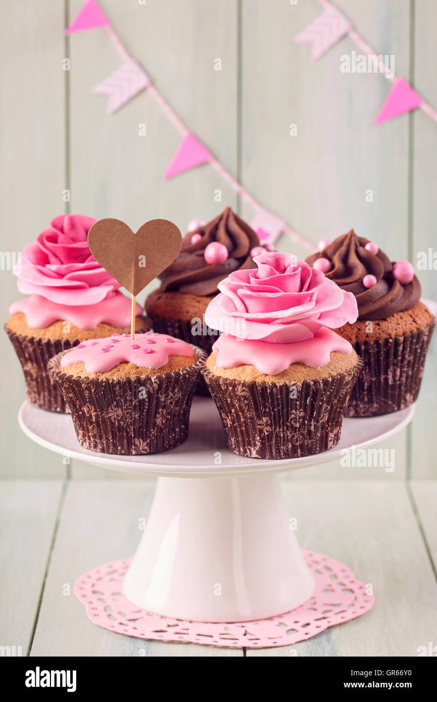 Cupcakes with sweet rose flowers and a cakepick for text - Stock Image
