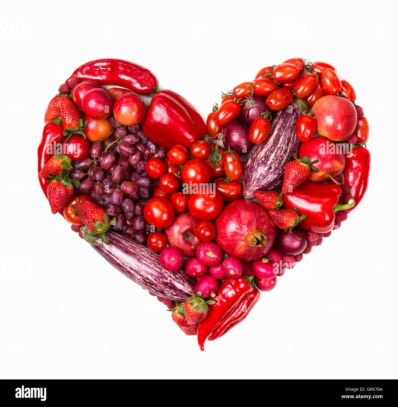 Heart of red fruits and vegetables isolated on a white background - Stock Image