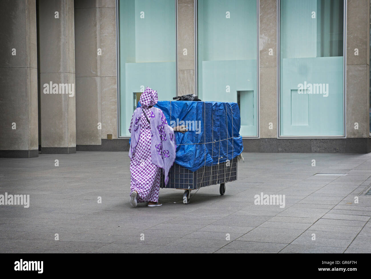 An anonymous African woman in ethnic dress pushes her cart on 47th Street in MIdtown Manhattan, New York City - Stock Image