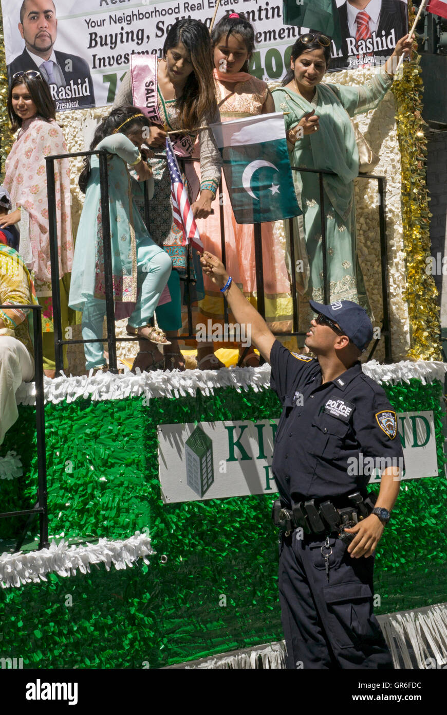 An New York City policeman retrieves an American flag for a young Pakistani girl at the Pakistan Day Parade in Manhattan. - Stock Image