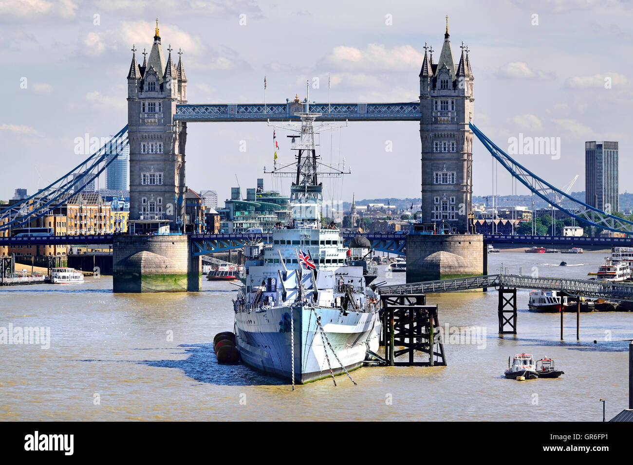 London, England, UK. HMS Belfast (in service 1938-1963: now part of the Imperial War Museum) and Tower Bridge behind - Stock Image