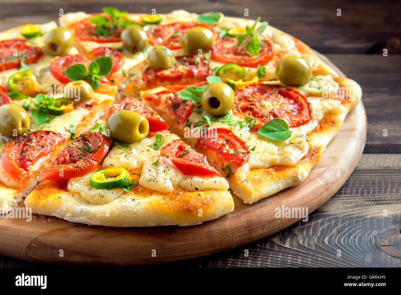 Homemade vegetable pizza with tomatoes, green olives, pepper, basil, oregano and cheese on wooden table with copy - Stock Image