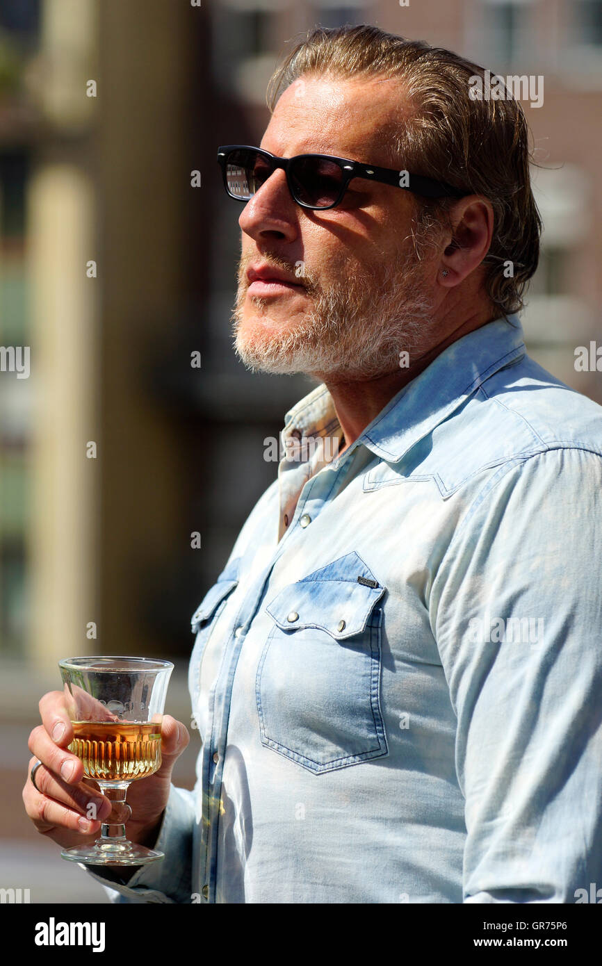 Man With A Denim Shirt Drink Alcohol - Stock Image