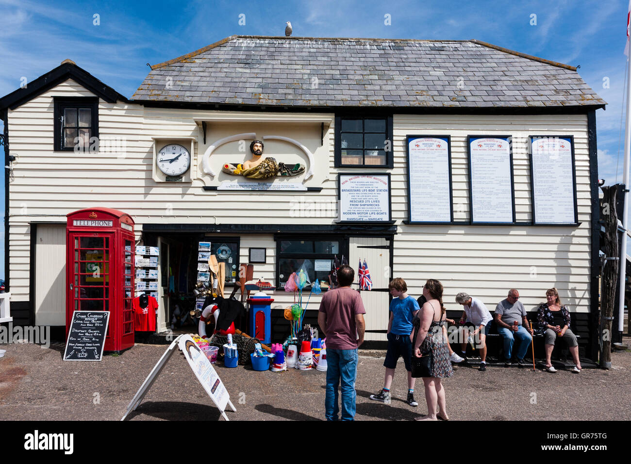 England, Broadstairs. The white wooden clapboard Boathouse on the harbour, with red telephone box outside and people - Stock Image