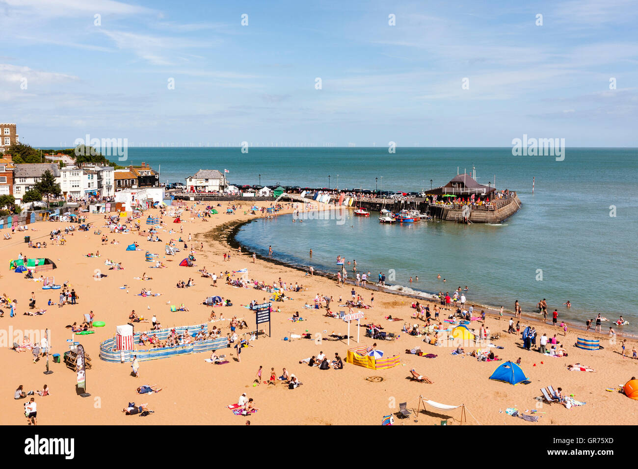 Broadstairs resort town in UK, the main beach with small harbour at one end. Hot summer day with lots of people - Stock Image