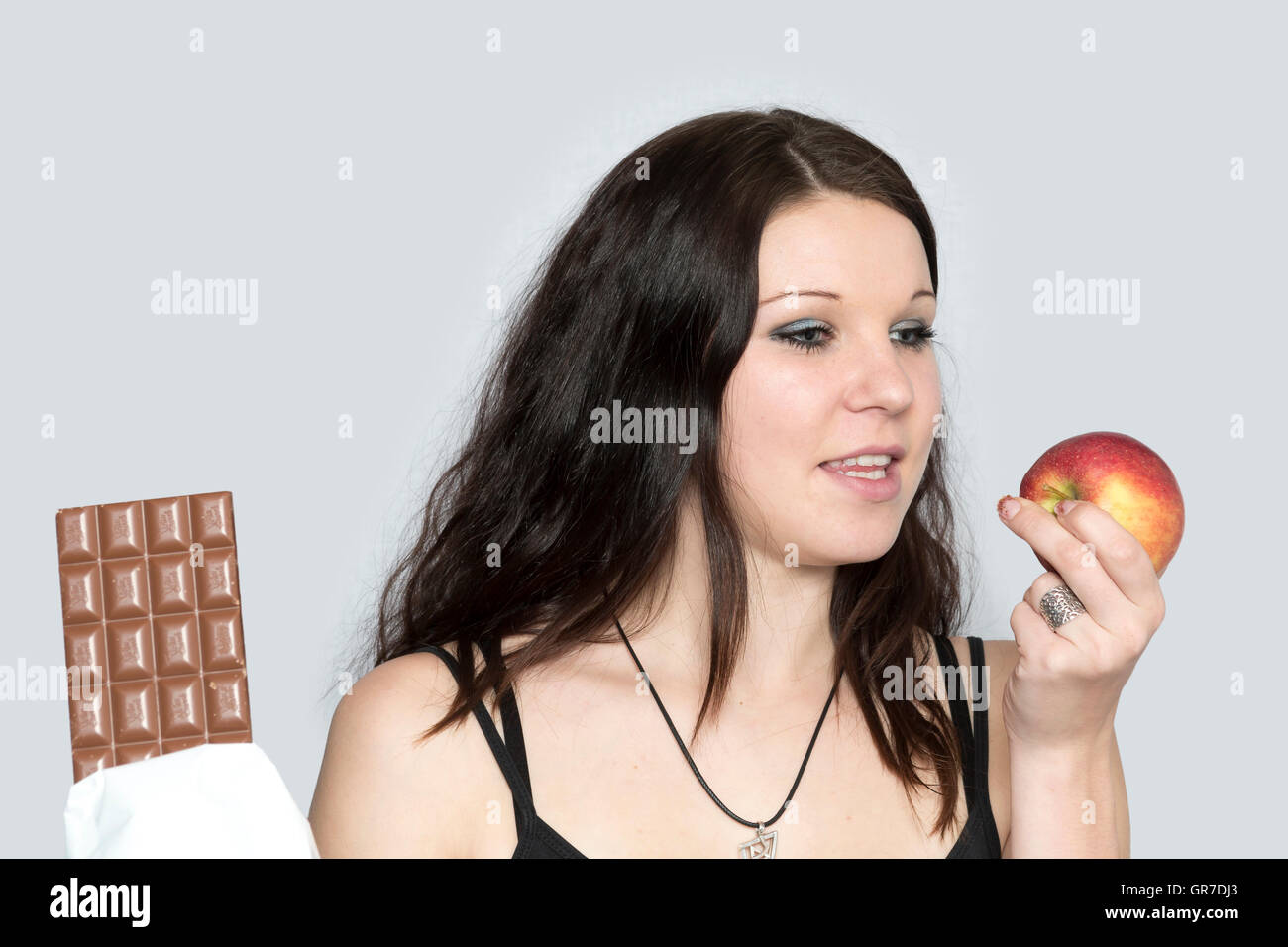 Woman Chooses Instead Of A Chocolate Bar Prefer An Apple - Stock Image