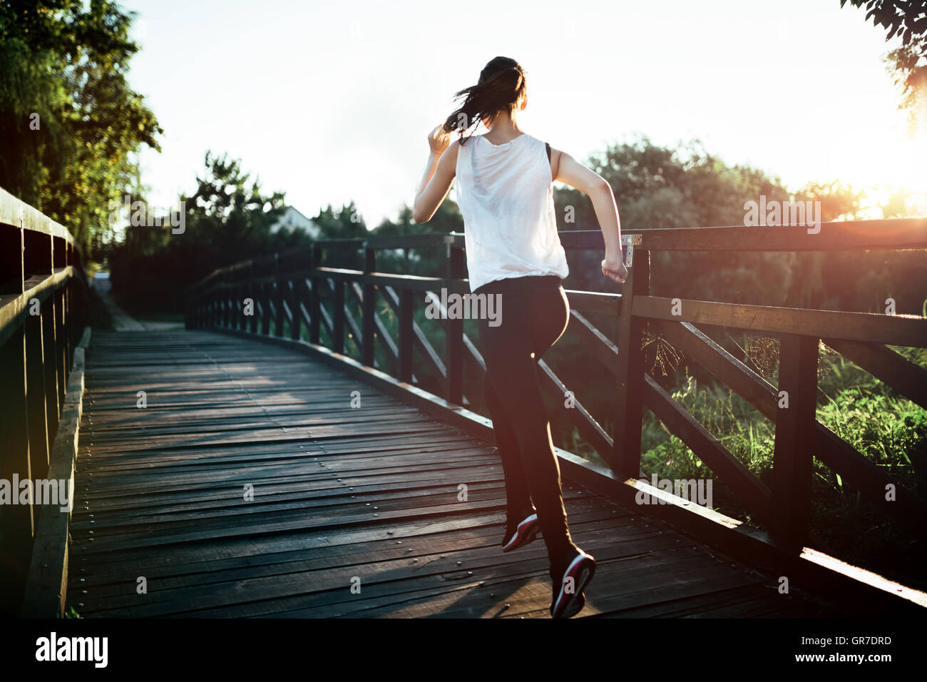 Beautiful athletic jogger crossing bridge - Stock Image